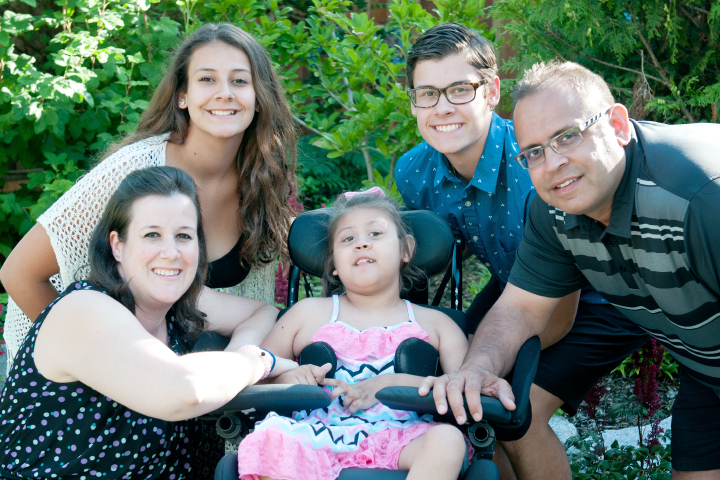 Canuck Place family and child in the garden outside the hospice